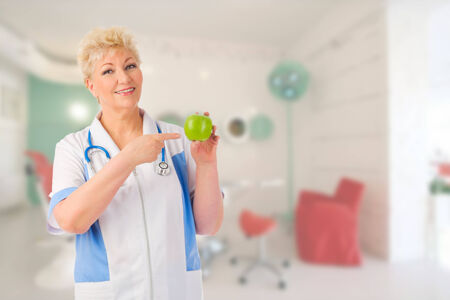 Mature doctor with green apple at medical office photo