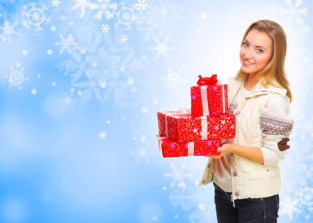 Young girl with gift boxes on blue winter background Stock Photo - 23171920