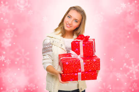 Young girl with gift boxes on red winter background Stock Photo - 23171921