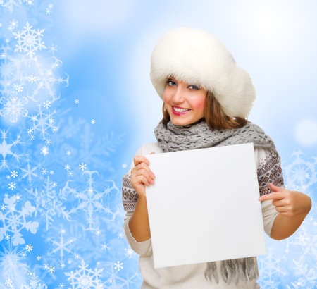 Young girl with empty card on blue winter background Stock Photo - 23171923