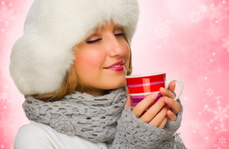 Young girl with mug on red winter background photo