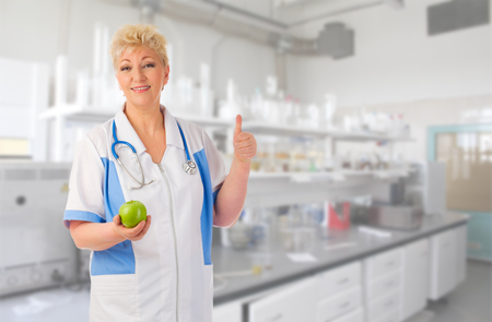 Mature doctor with green apple at lab photo