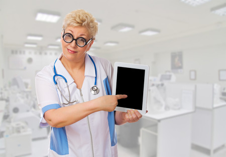 Funny mature doctor in nerd glasses with tablet PC at lab photo
