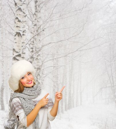 Young smiling girl shows pointing gesture at snowy forest Stock Photo - 23419279