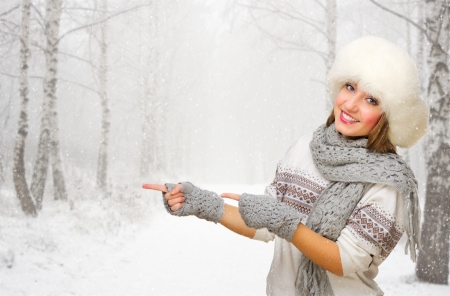 Young smiling girl shows pointing gesture at snowy forest photo