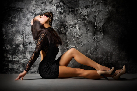 Fashion portrait of young girl on grey wall photo