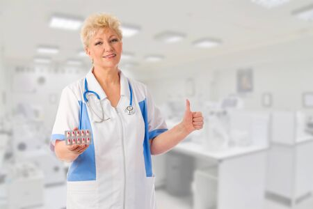 Mature doctor with pills at medical office photo
