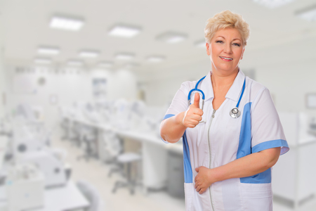 Mature doctor shows ok gesture at lab photo