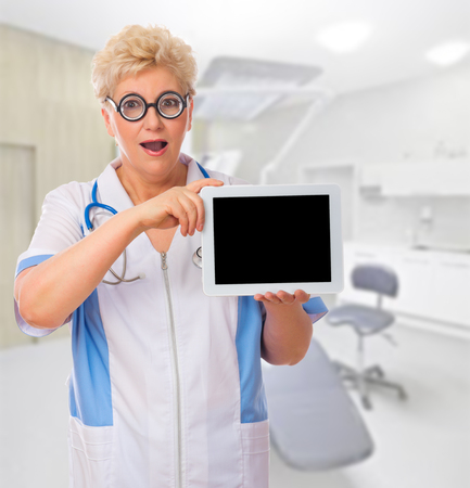 Mature doctor with tablet PC at medical office photo