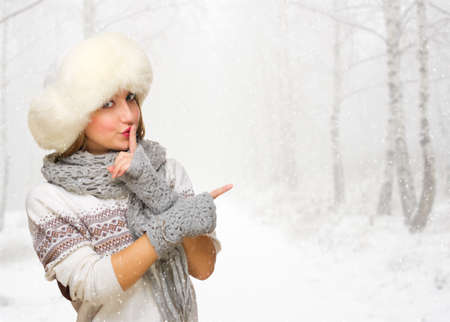 Young girl shows pointing gesture at winter forest Stock Photo - 23955479
