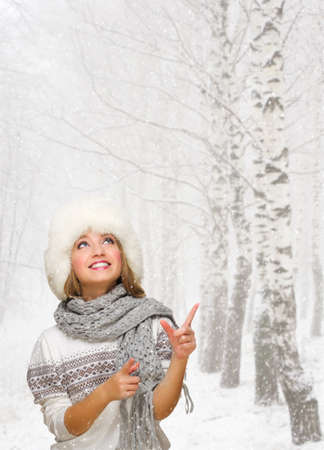 Young girl shows pointing gesture at winter forest photo