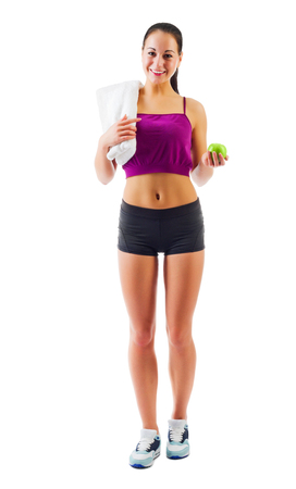 Young sporty girl with towel and apple isolated photo