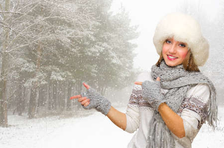 Young woman in fur hat shows pointing gesture at snowy forest photo