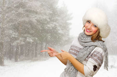 Young smiling girl shows pointing gesture at snowy forest Stock Photo - 24474973