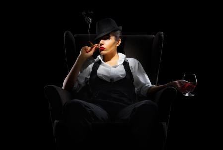 Maffiosi vrouw met sigaar en cognac glas geïsoleerd Stockfoto