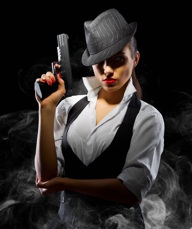 Dangerous and beautiful criminal girl with gun on smoky background photo