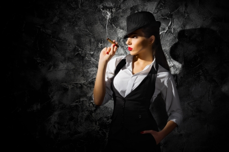 Dangerous and beautiful criminal girl with cigar on grey wall photo