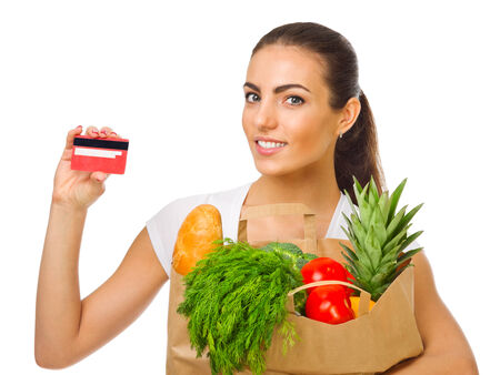 Young girl with fruits, vegetables and plastic card isolated photo