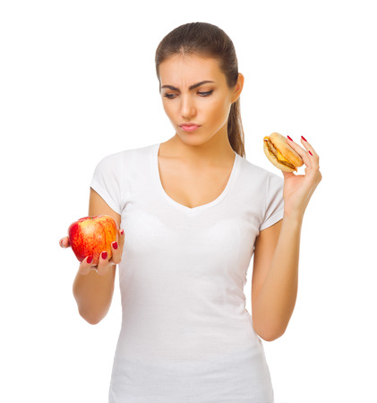 Young doubting girl with apple and hamburger isolated photo