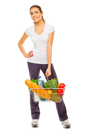 Young girl with full shop basket isolated photo