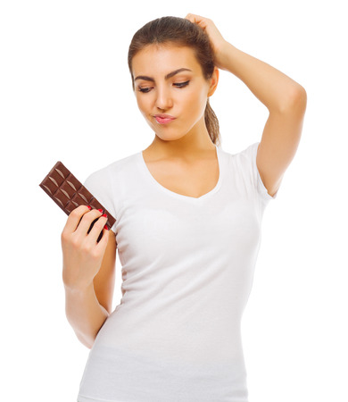Doubting young girl with chocolate isolated Stock Photo