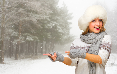 Young girl at snowy winter forest shows pointing gesture photo