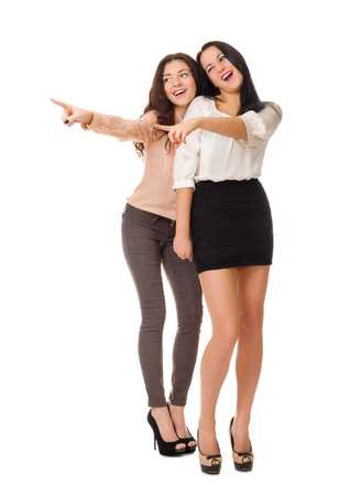teases: Two young girl shows pointing gestures isolated Stock Photo