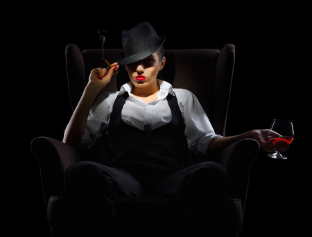 Mafiosi woman with cigar and cognac glass isolated