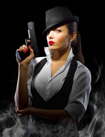 Portrait of young woman in manly style with gun and smoke photo