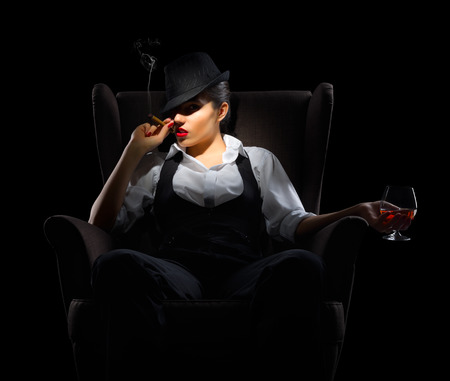 Young woman with cigar and brandy glass on chair isolated