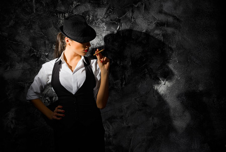 Young woman with hat and cigar on grey wall photo
