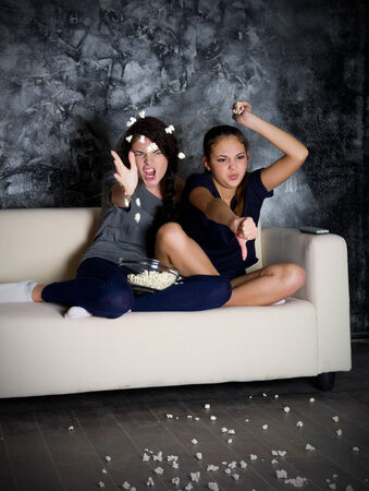 Two angry girls looks TV in dark room photo