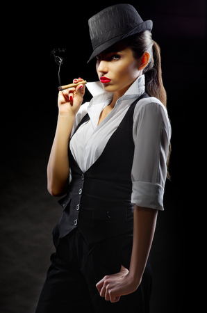 Young woman with cigar on black photo