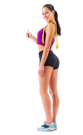 Young sporty girl with centimeter tape isolated photo