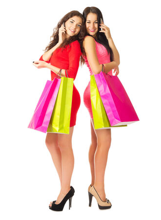 Two young girls with mobile phones and bags isolated photo