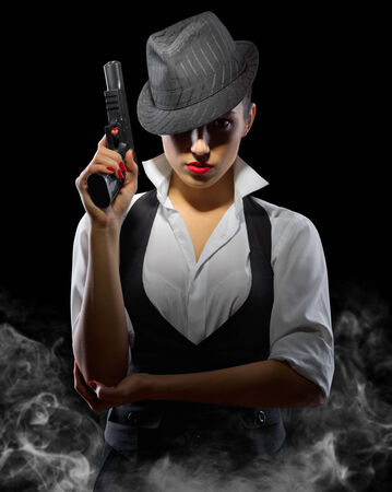 Young woman with gun on black photo