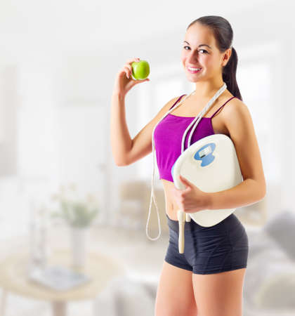 weight room: Sporty girl with apple and scales at light room