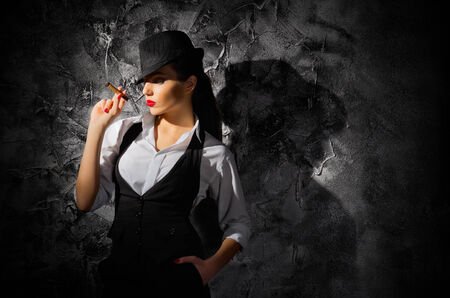 Woman with cigar on grey wall background photo