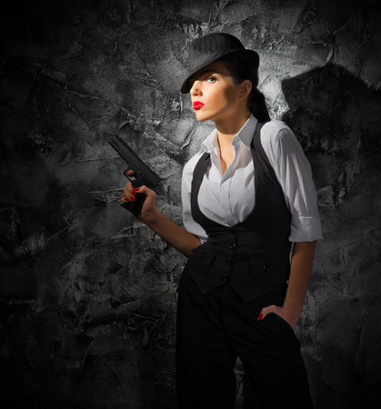 Woman with gun on grey wall background photo
