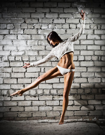 Dancing young woman on grey wall (dark version) photo