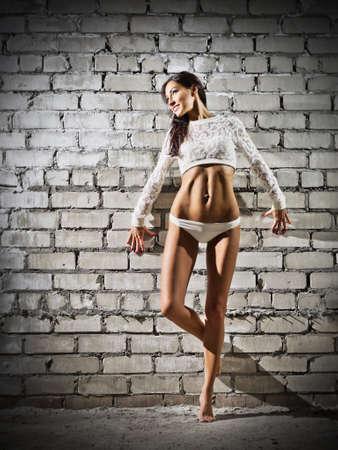 Young woman on grey brick wall (dark version) photo