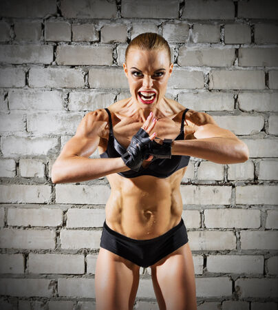 Muscular woman on grey brick wall (normal version) photo