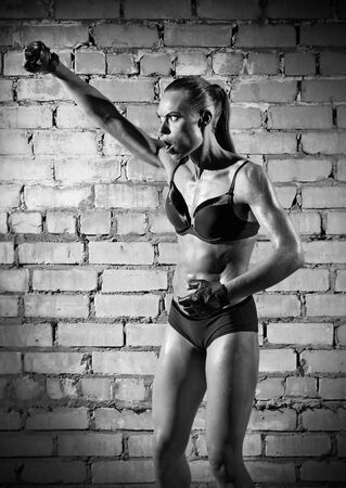 Muscular woman on grey brick wall (monochrome version) photo