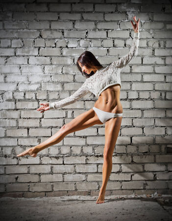 Dancing young woman on grey wall (normal version) photo