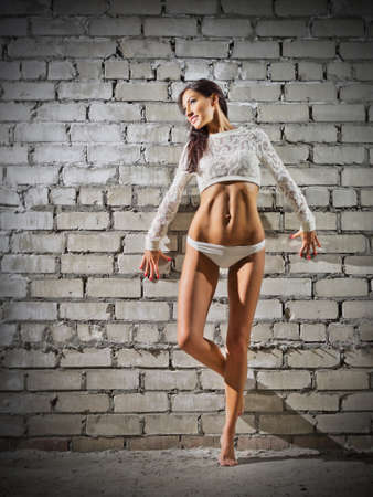 Young woman on grey brick wall (normal version) photo
