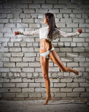 Young dancing woman on grey brick wall background (normal version) photo