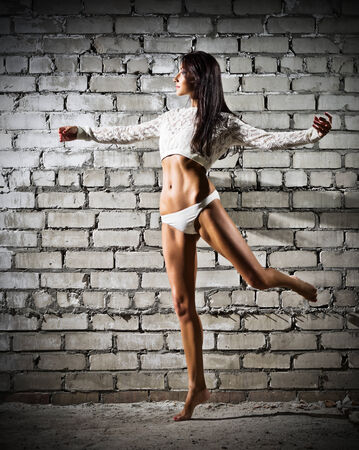 Young dancing woman on grey brick wall background (dark version) photo
