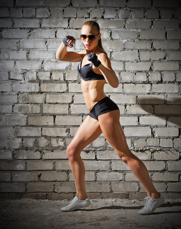 Muscular sporty woman on grey brick wall (normal version) photo