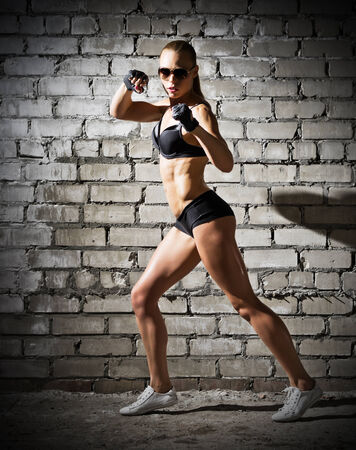 Muscular sporty woman on grey brick wall (dark version) photo