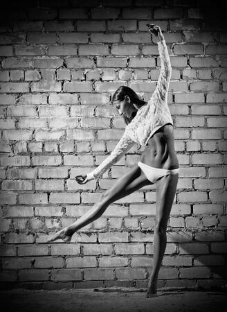 Young dancing woman on grey brick wall (monochrome version) photo